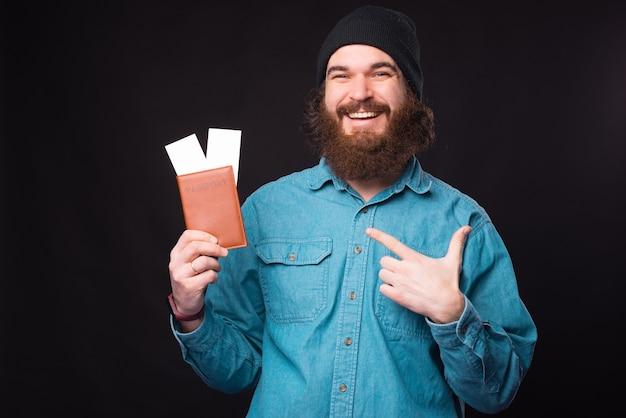 Foto van lachende hipster man wijzend op paspoort en tickets