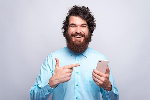 Foto van lachende jonge bebaarde hipster man wijzend op smartphone op witte muur