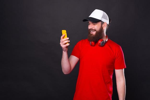 Foto van lachende jonge man met baard in rood t-shirt in de buurt van zwarte achtergrond met smartphone