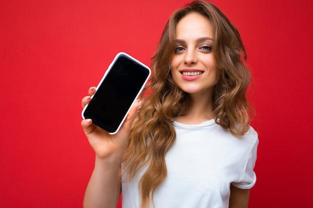 Foto van lachende jonge vrouw knap gekleed casual stijlvolle outfit staande geïsoleerd