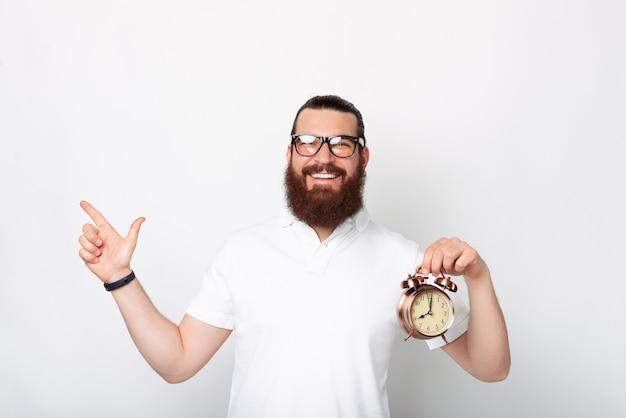 Foto van lachende knappe bebaarde man met wekker en weg te wijzen