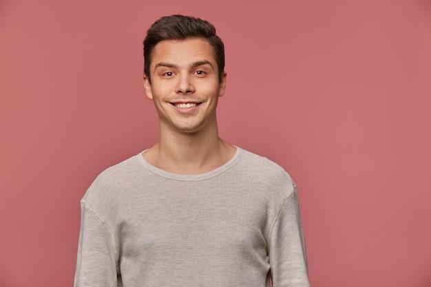 Foto van lachende knappe jonge kerel draagt in lege lange mouw, ziet er vrolijk en blij uit, kijkt naar de camera met gelukkige uitdrukking, staat op roze achtergrond en glimlachen.