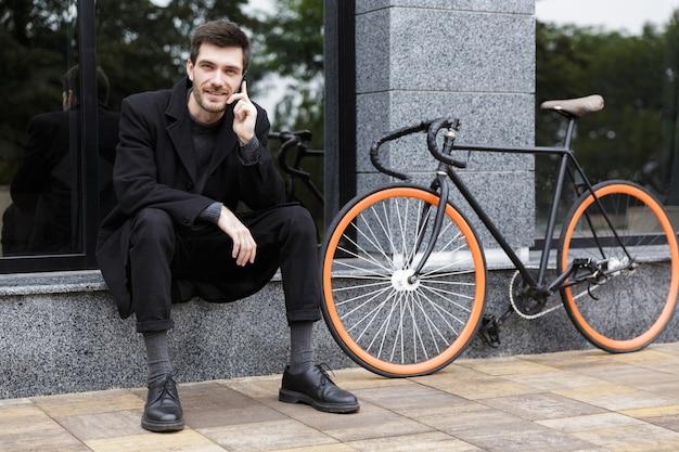 Foto van lachende man 20s met behulp van mobiele telefoon, zittend buiten met fiets