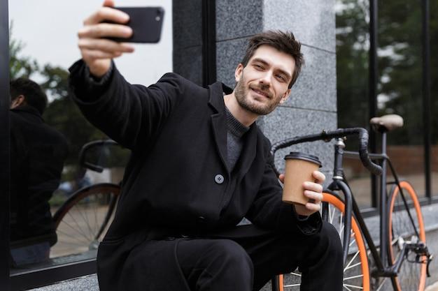 Foto van lachende man 20s selfie te nemen op de mobiele telefoon, zittend buiten met fiets