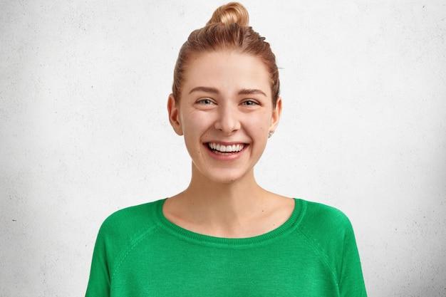 Foto van lachende schattige europese vrouw met haarknoop, draagt felgroene trui, brede glimlach en witte tanden, blij om een onvergetelijke dag met minnaar door te brengen