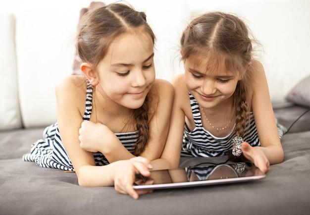 Foto van lachende schoolmeisjes die op de bank liggen en op tablet spelen