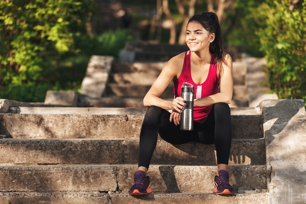 Foto van lachende sportvrouw ontspannen op trappen na de training