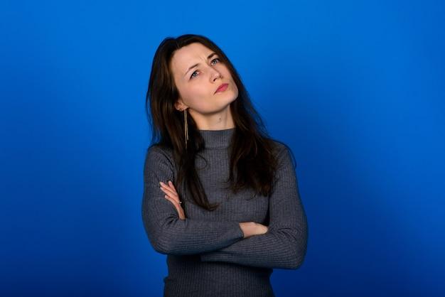 Foto van lachende, vrolijke jonge vrouw in grijze jurk op blauwe ruimte