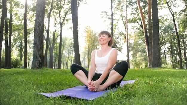 Foto van lachende vrouw die yoga- en fitnessoefeningen doet. mensen van middelbare leeftijd die voor hun gezondheid zorgen. harmonie van lichaam en geest in de natuur