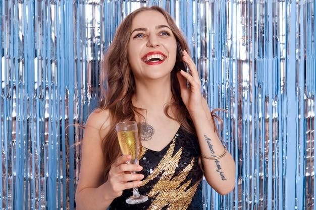 Foto van lachende vrouw jurken zwarte outfit poseren met glas in en en praten via mobiele telefoon geïsoleerd op ruimte met zilver glitter klatergoud.