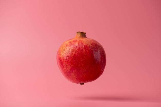 Foto van lekkere heerlijke mooie rijpe heldere granaatappel vliegen in de lucht geïsoleerd over felle kleur achtergrond. sjabloon patroon concept