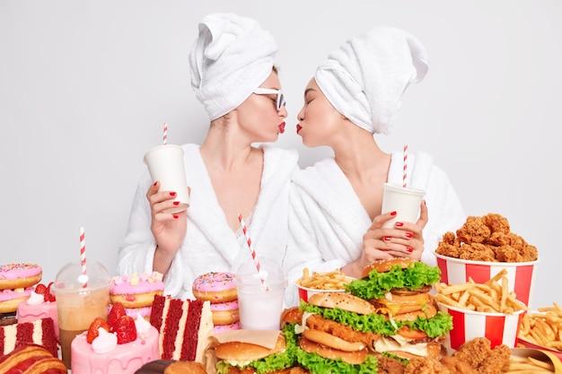 Foto van lesbische vrouwen die elkaar kussen, frisdrank drinken, genieten van fastfood