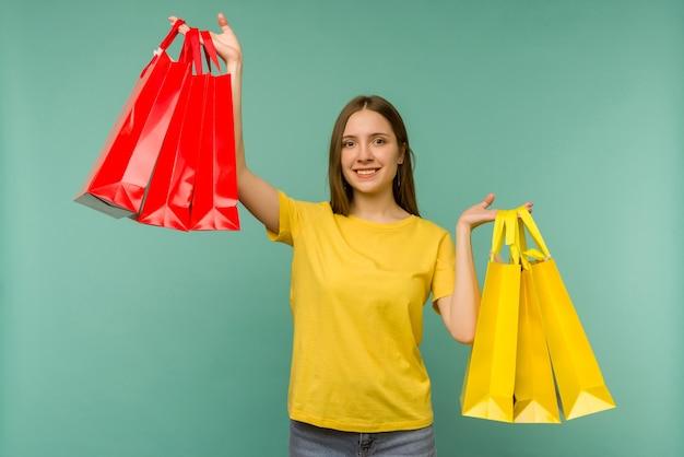 Foto van leuk charmant meisje aantrekkelijk vrolijk meisje dat net is gaan winkelen en dolblij en opgewekt is terwijl ze met blauw is
