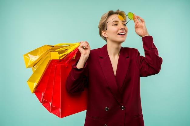 Foto van leuk charmant meisje aantrekkelijk vrolijk meisje dat net met winkelen is beland en dolblij en vrolijk is terwijl geïsoleerd met blauwe achtergrond.