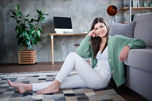 Foto van leuk meisje zit tapijt in moderne woonkamer binnenshuis