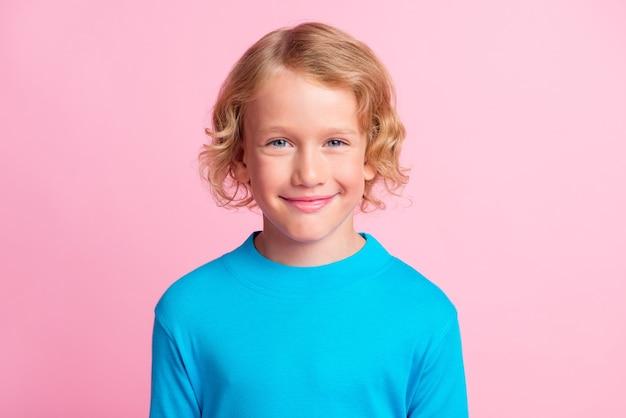 Foto van lief klein kind kijkt camera grappig lachend draag blauwe coltrui geïsoleerde pastelroze kleur achtergrond