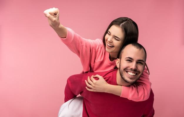 Foto van lief paar knuffelen elkaar en glimlachen. man en vrouw zijn verliefd, vrouw doet alsof ze superheld op zijn rug is, geïsoleerd op roze achtergrond.
