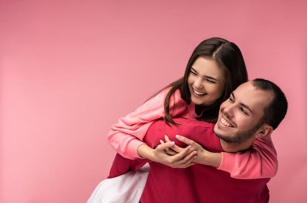Foto van lief paar knuffelen elkaar en glimlachen. mannetje en vrouwtje zijn verliefd, geïsoleerd op roze achtergrond.