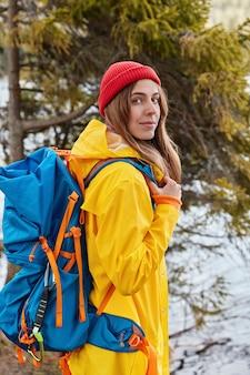 Foto van lovabe jong vrouwelijk model draagt rode hoed, gele regenjas, draagt grote tas, vormt tegen dennenboom op heuvel