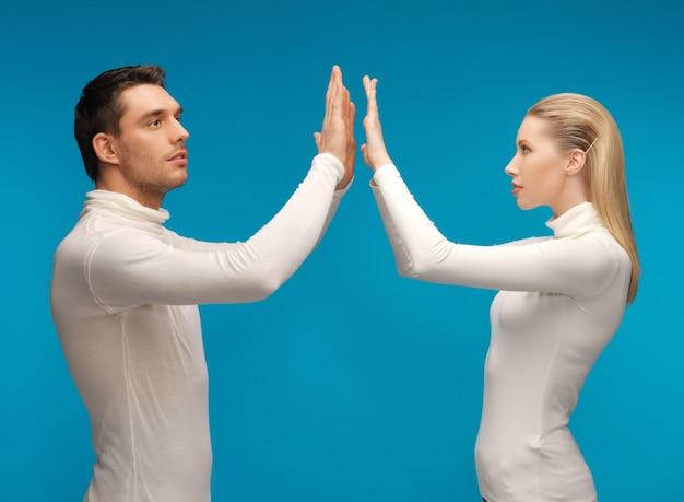 Foto van man en vrouw die met iets denkbeeldigs werken.