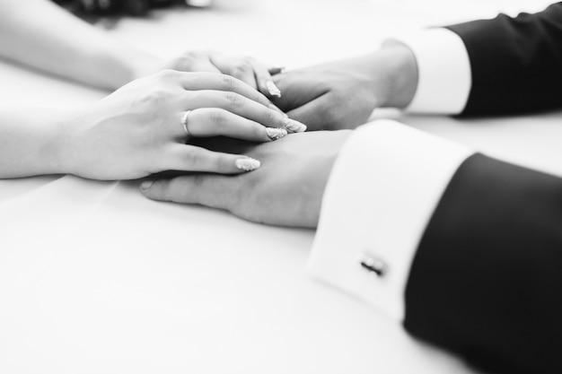 Foto van man en vrouw hand in hand. huwelijksplechtigheid. bruidegom en bruid. vrouw en man. zwart-wit foto. detailopname.