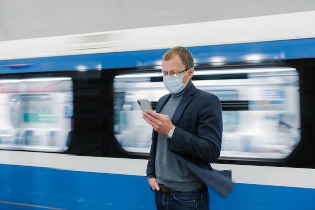 Foto van man in bril en beschermend medisch masker, gebruikt moderne telefoon, reist met openbaar vervoer, staat trein in beweging op perron, krijgt online informatie over nieuw covid-19 virus