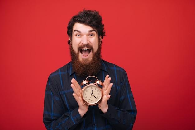 Foto van man met baard klaar beginnen te werken. tijd om te werken. rode muur