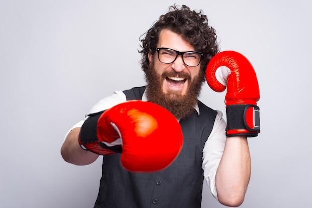 Foto van man met baard pak dragen en ponsen met bokshandschoenen