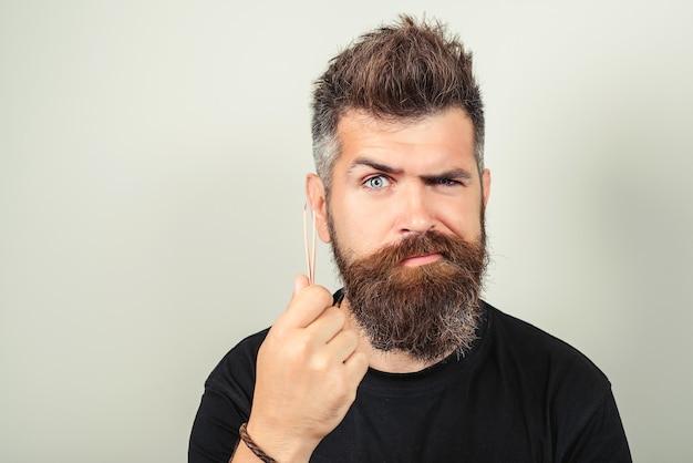 Foto van man plukt wenkbrauwen epileert met pince. close-up shot van verbaasde ongeschoren jonge kerel gebruikt prima voor het polijsten van nagels. knappe man probeert zijn wenkbrauwen te plukken, geïsoleerde blauwe achtergrond.
