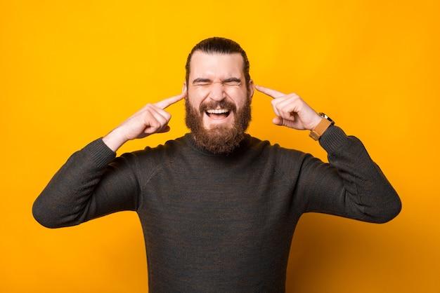 Foto van man vingers in de oren steken en niets luisteren