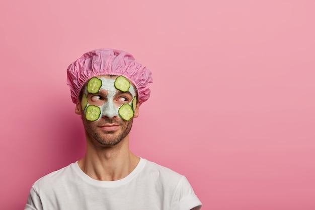 Foto van mannelijk model opzij geconcentreerd, heeft schoonheidsprocedures, past kleimasker en komkommers toe op de teint