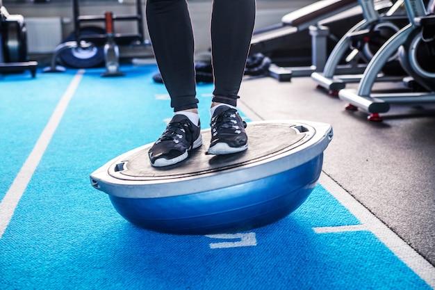 Foto van mannelijke benen op bosu-bal in fitnessstudio
