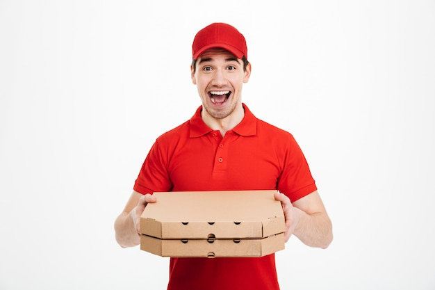 Foto van mannelijke werknemer van bezorgservice in rood t-shirt en pet eten bestellen en twee afhaalpizzadozen houden, geïsoleerd over witte ruimte
