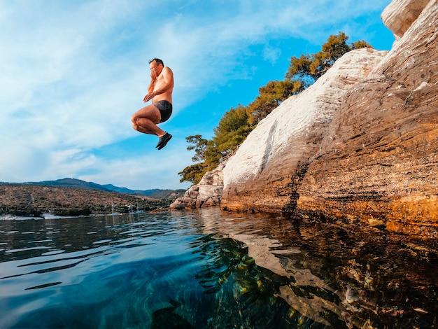 Foto van mannen die in medio lucht in water springen