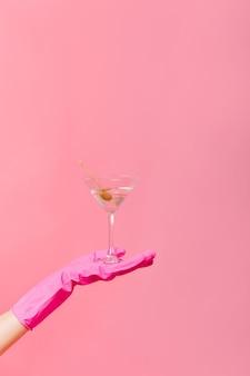 Foto van martiniglas met in hand olijf op roze muur