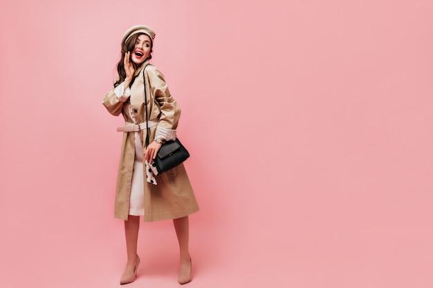 Foto van meisje gekleed in lichte trenchcoat en voelde baret poseren met zwarte handtas op geïsoleerde achtergrond.