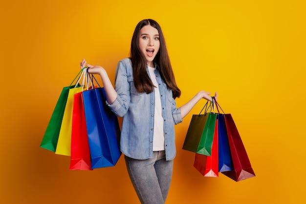 Foto van meisje met boodschappentassen op gele achtergrond
