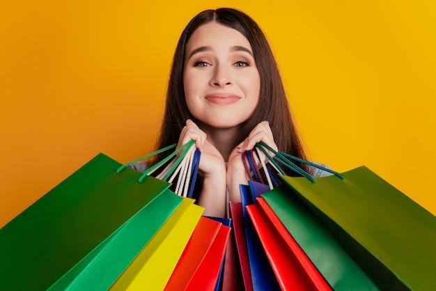 Foto van meisje met boodschappentassen schattig gezicht op gele achtergrond