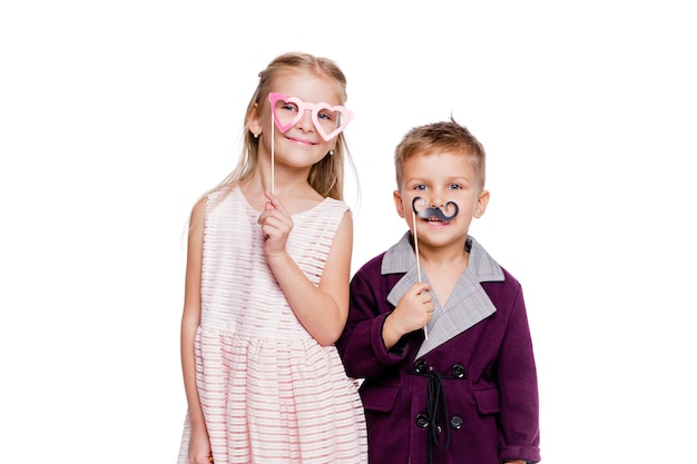 Foto van meisje met een hartvormige kartonnen bril en een jongen met een kartonnen snor poseren