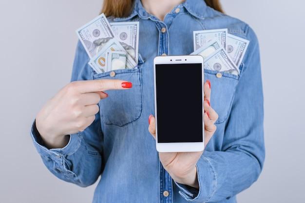 Foto van meisje met geld in zakken smartphone demonstreren met wijsvinger geïsoleerd grijze achtergrond