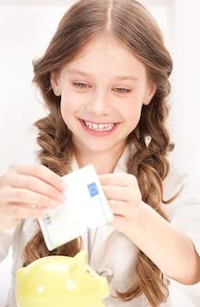 Foto van meisje met spaarvarken en geld