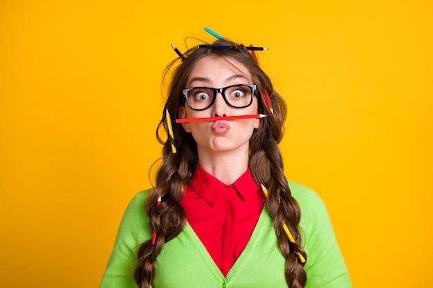 Foto van meisje rommelig kapsel grappig gezicht uitdrukking potlood neus geïsoleerd op gele kleur achtergrond