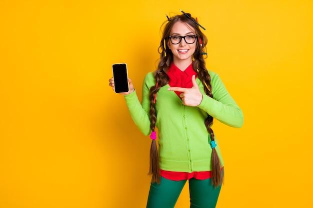 Foto van meisje rommelig kapsel punt vinger smartphone draag shirt broek geïsoleerde gele kleur achtergrond