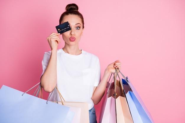 Foto van meisje winkelcentrum klant sluit bedek haar ogen debetkaart stuur lucht kus hold bags