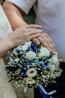 Foto van met bruidsboeket jong getrouwd stel hand in hand ceremonie trouwdag