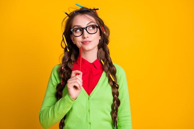 Foto van minded nerd meisje ziet er lege ruimte uit, denk dat je een groen shirt draagt dat op een felgele achtergrond is geïsoleerd