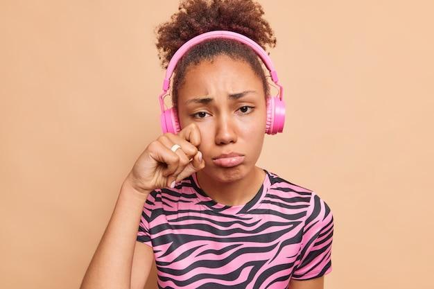 Foto van misnoegde mokkende vrouw snikt en veegt tranen weg omdat ze diepbedroefd is van streek na het uiteenvallen
