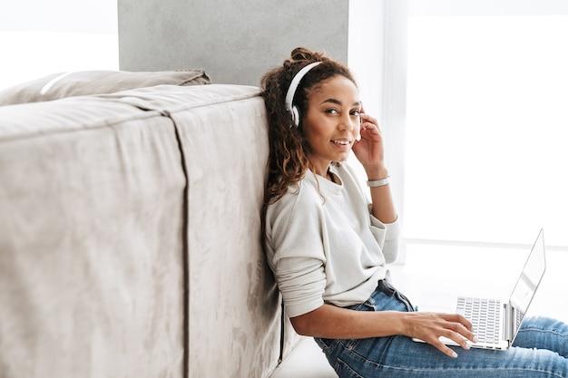 Foto van moderne afro-amerikaanse vrouw hoofdtelefoon dragen met behulp van laptop, zittend op de vloer in de lichte woonkamer