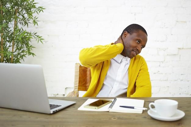 Foto van moderne modieuze jonge donkere zakenman die nek wrijft, zich gefrustreerd en onzeker voelt over iets, zittend op de werkplek met geopende laptop, dagboek, mok en mobiele telefoon op bureau