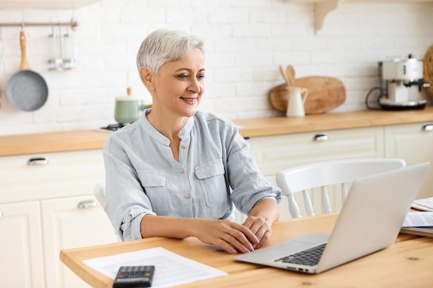 Foto van moderne mooie gepensioneerde vrouw met behulp van draadloze internetverbinding op draagbare computer, zittend aan tafel in een stijlvol keuken interieur, wegkijken met doordachte peinzende gezichtsuitdrukking